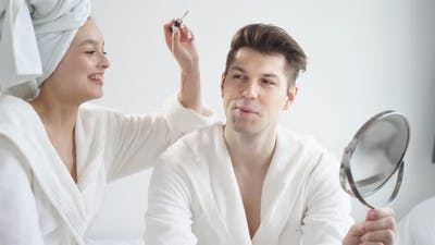 Portrait of Funny Couple Doing Makeup at Home