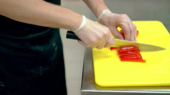 Cover Image for CU: Cook Very Quickly Cuts a Fresh Bulgarian Red Pepper with a Knife.