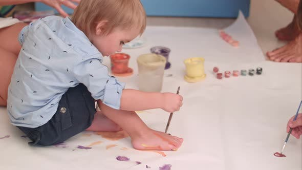 Thumbnail for Cute Little Baby Boy Painting His Feet on a Large Blank White Paper
