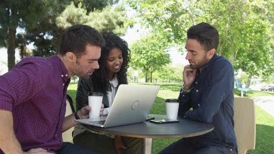 Thumbnail for Three friends sitting at outdoor caf_ talking and using laptop and cell phone