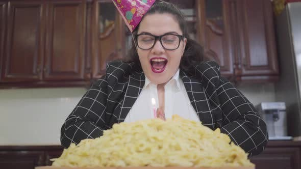 Thumbnail for Portrait Cute Fat Happy Girl in a Festive Cap and Stylish Glasses Sitting at the Table in the
