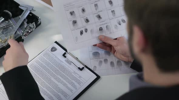 Thumbnail for Detective Watching Fingerprints on Paper, Using Magnifying Glass, Solving Murder