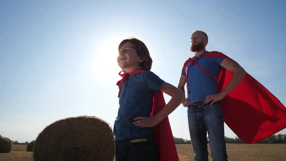 Serious Dad and Son in Superhero Pose on Field