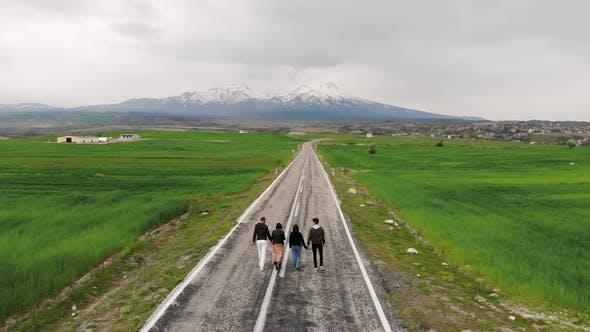 Drone footage: Travelers Walking Along A Road