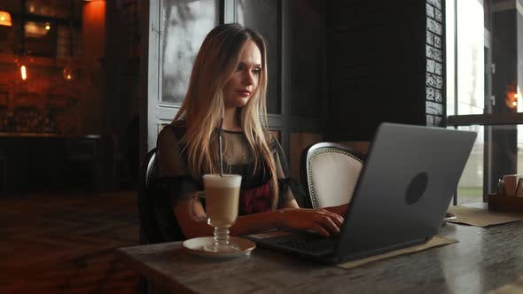 Thumbnail for Beautiful Woman Working on Her Laptop on a Stylish Urban Restaurant