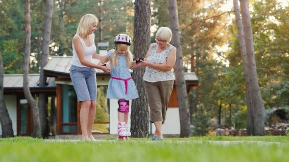 Thumbnail for Mom and Grandmother Teach the Girl To Skate on Roller Skates. Friendly Family, Communication of