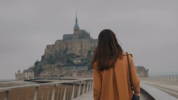Beautiful Elegant Happy Tourist Woman Looking Back at Camera, Walking To Amazing Mont Saint Michel