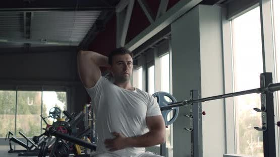 Konzentriertes Muskelsportlertraining im Fitnessstudio, Training mit Hanteln