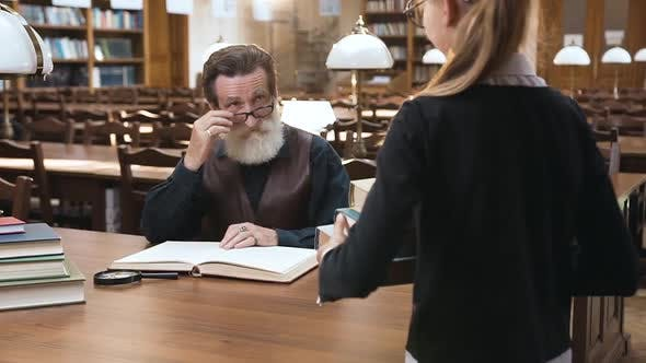 Thumbnail for Senior Bearded Man in Glasses Sitting at the Library Table While His Nice Teen Granddaughter