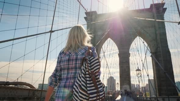 Thumbnail for A Woman Walks Along the Brooklyn Bridge, the Sun Illuminates the Pillars of the Bridge