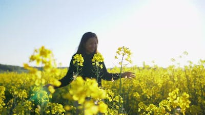 Asian woman running on track and touching flower in yellow field
