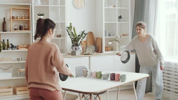 Zwei weibliche Freunde spielen Tischtennis mit Geschirr zu Hause