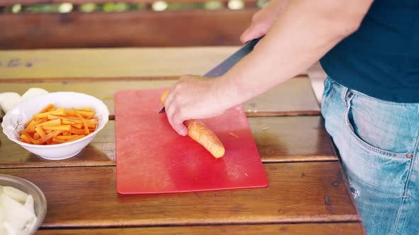 Thumbnail for Close-up: Guy Is Cooking Pilaf. He Is in a Summer House, Cuts Carrots, on a Red Cutting Board