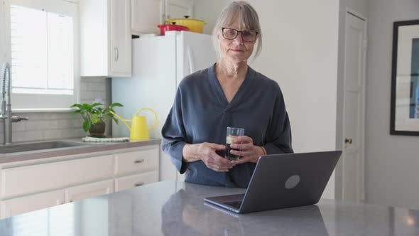 Thumbnail for Woman wearing glasses with laptop computer on kitchen counter holding coffee