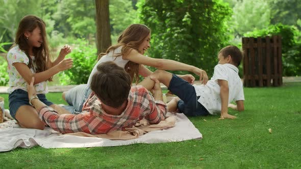 Thumbnail for Parents Playing with Children in Park. Kids and Parents Lying on Blanket