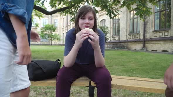 Thumbnail for Relaxed Plump Boy Sitting on Bench with Sandwich As Unrecognizable Aggressive Classmates Knocking
