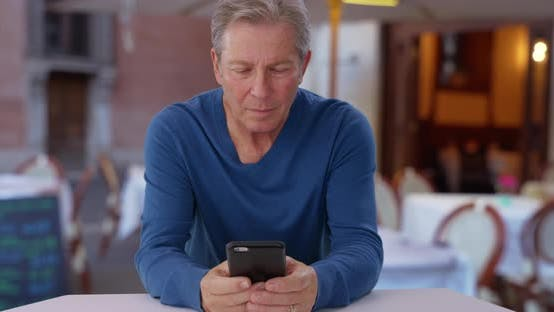 Thumbnail for Caucasian male senior uses smartphone while sitting at restaurant in Europe