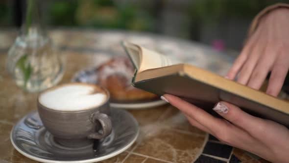 Thumbnail for Junge Geschäftsfrau sitzt in einem Café und ein Buch lesen Nahaufnahme. Mädchen mit Kaffee und ein Brötchen auf