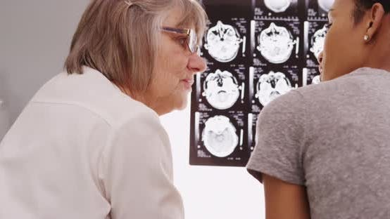 Thumbnail for Experienced radiologist and patient looking at x rays
