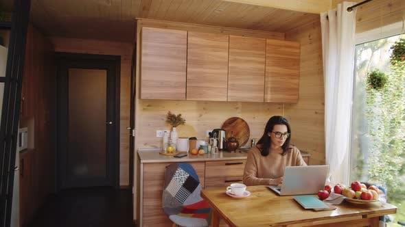 Junge Frau nutzt Laptop am Küchentisch im Landhaus