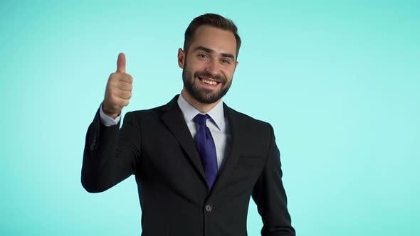 Thumbnail for Positive young businessman smiles to camera. Man showing thumbs up sign over blue