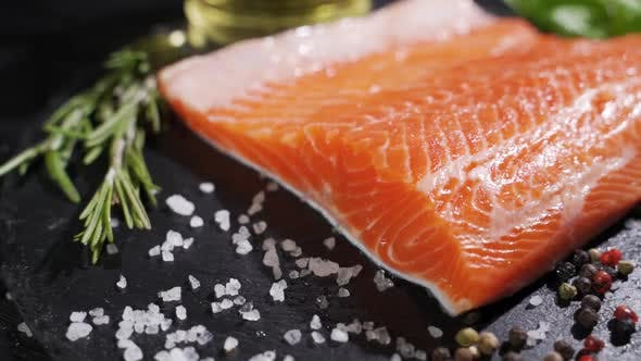 Cover Image for Preparation of Salmon Steak. Spice and Salt Sprinkled on a Raw Piece of Salmon.