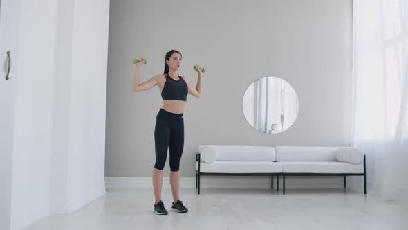 Thumbnail for Raise the Dumbbells Over Your Head Performing Exercises for the Shoulders. Training at Home