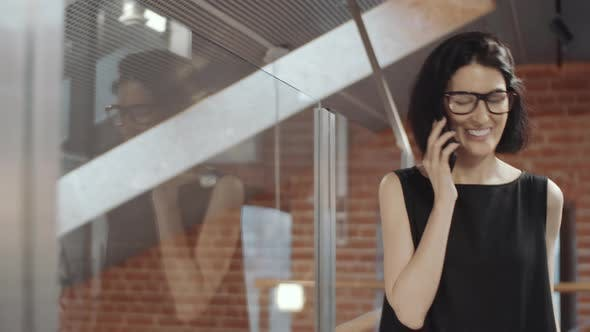 Thumbnail for Smiling Businesswoman Walking in Office and Talking on Cell Phone