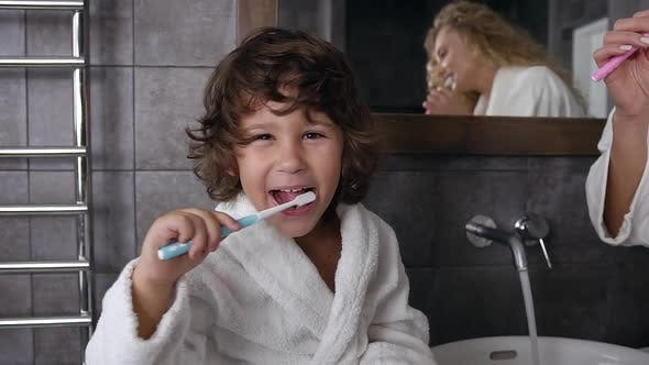 Thumbnail for Cheerful Little Boy with Curly Hair in a White Coat is Brushing His Teeth with Toothpaste