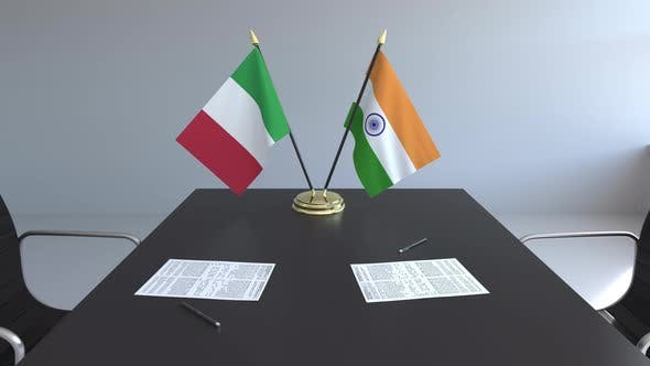 Flags of Italy and India and Papers on the Table