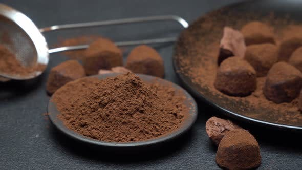 Thumbnail for Chocolate Truffles Candies and Cocoa Powder on Dark Concrete Background