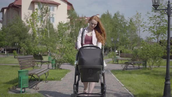 Thumbnail for Young Happy Redhead Mother Walking with Baby Carriage and Smiling Along the Street on a Nice Spring