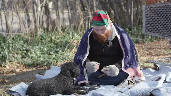 Thumbnail for Homeless man eating bread and feeding dog