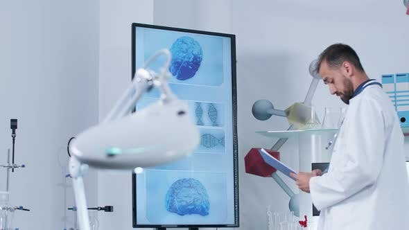 Thumbnail for Dolly Shot of a Scientist in Modern Research Center Looking at Big TV