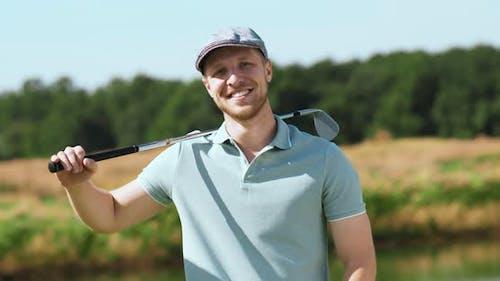 Porträt eines jungen bärtigen Mannes, der mit Golfstock posiert, lächelnd zur Kamera, Tracking Shot