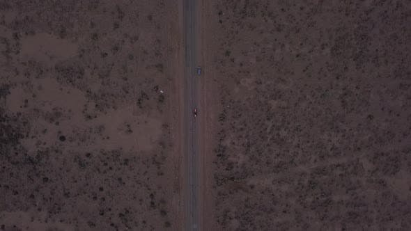 Thumbnail for AERIAL: Birds View Flight Over Lonely Abandoned Desert Road with Red Car Driving in the Distance