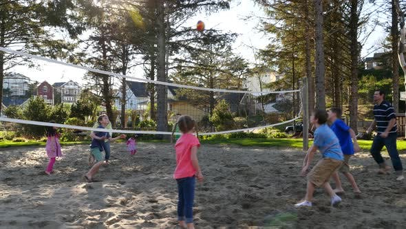 Thumbnail for Family playing at sand volleyball court