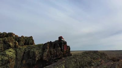 View of a Human Climbing to the Top of a Mountain