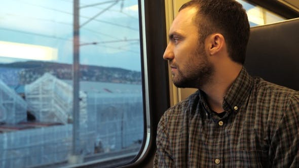 Thumbnail for Confident serious man looks out the window of a train