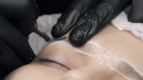 Permanent Makeup. Permanent Tattooing of Eyebrows. Cosmetologist Applying Permanent Make Up on
