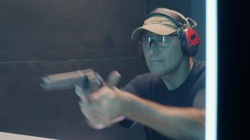 Mature Man Firing Revolver in Shooting Range