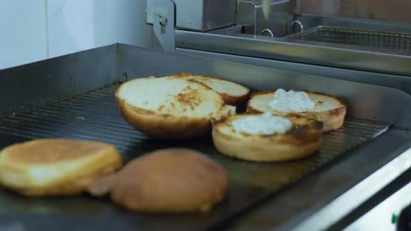 Thumbnail for Cooking Hamburger, Cook in Gloves Pour Sauce From a Bottle Into Buns for Making Grilled Burger in