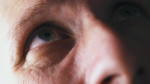 Thumbnail for Man with Green Eyes Looks Up Under Bright Electric Light