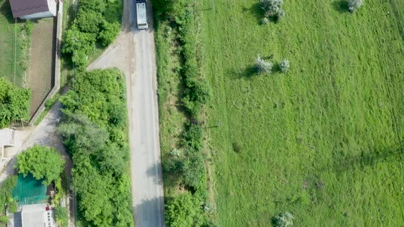 Thumbnail for Top Down Aerial View Following a Bus on a Road in a Rural Area