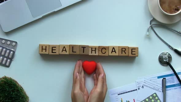 Thumbnail for Healthcare Word on Cubes, Doctors Hands Putting Toy Heart on Table, Cardiology
