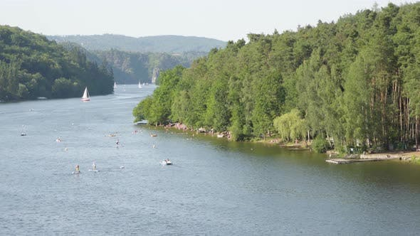 Cover Image for A View of a Wide Rive Surrounded By Mountains and Forests, People Swim and Enjoy Water By the Coast
