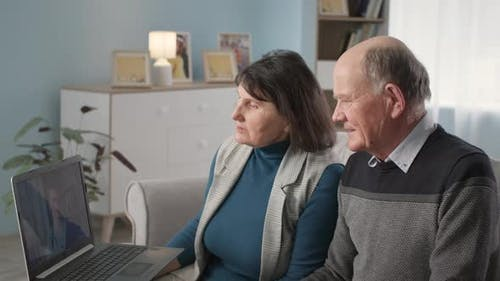 Male and Female Retirees at Medical Consultation are Talking on Webcam with Attending Physician