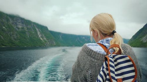 A Woman Stands at the Stern of a Cruise Ship, Looks at the Retreating Rocks and Waves of the Fjord