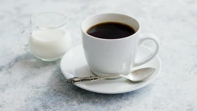 Cup of Coffee and Pitcher of Milk