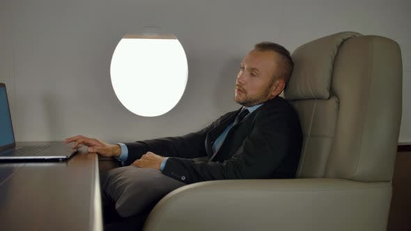 Thumbnail for Rich Entrepreneur Working on Notebook Inside of Luxury Jet